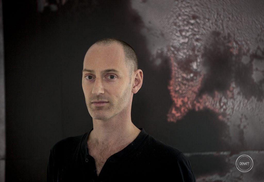 Portrait de l'artiste Sylvain Polony devant une de ses créations