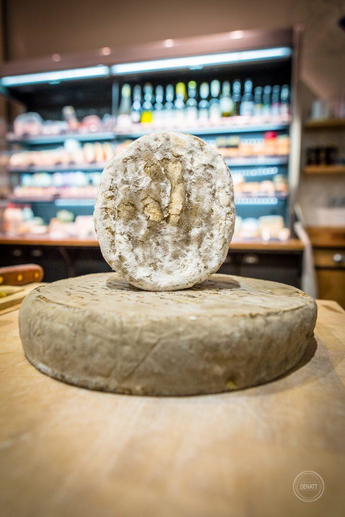 Deux fromages affinés sur le comptoir de chez Charlicot fromagerie pour reportage métier