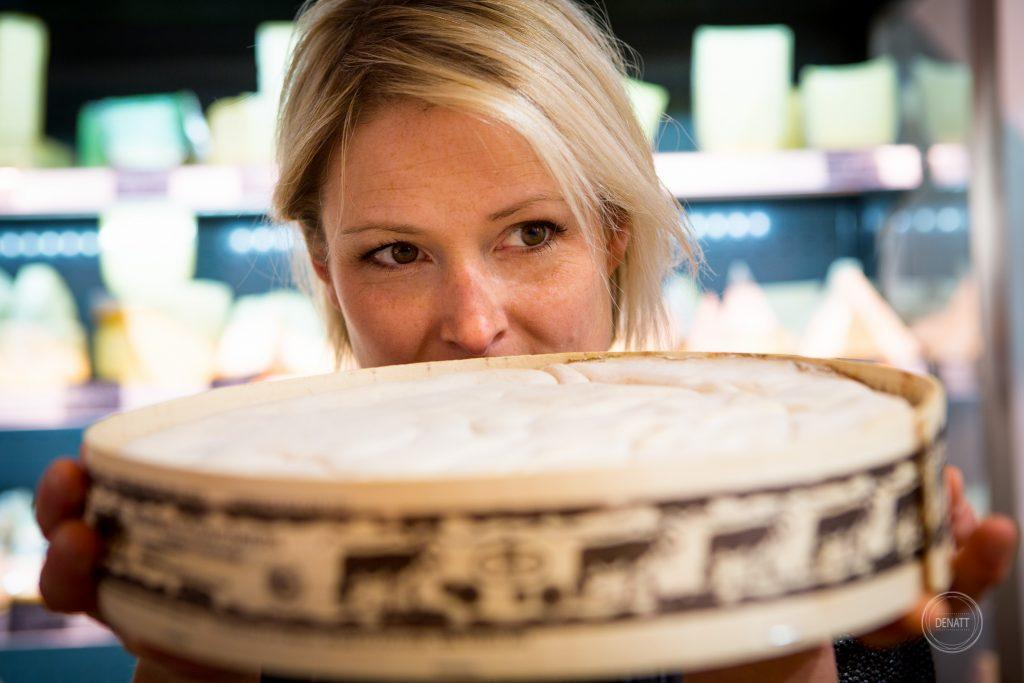 Portrait de Charlène portant un fromage dans sa fromagerie Charlicot. photo portrait