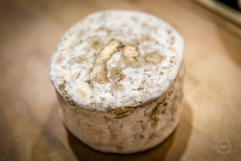 photo d'un fromage rond à la croûte gouteuse posé sur le comptoir de Charlicot à Paris