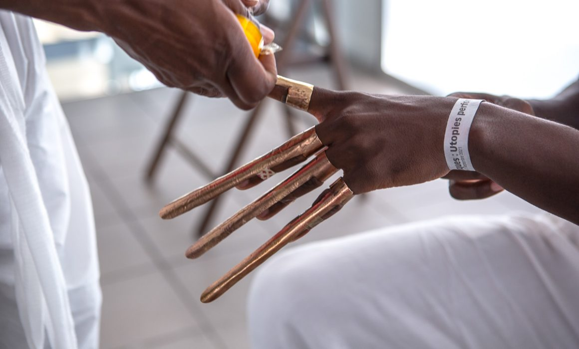 Accessoires métal sur main d'artiste pour performance collaborative de l'artiste Amin Gulgee